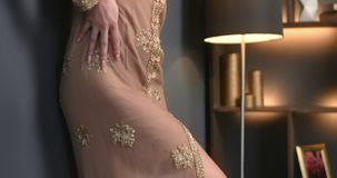 Woman stands near the wall in night dress and runs her hand over it, dress embroidered with gemstones, stylish sexy stock video