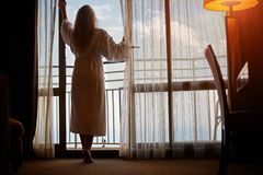 Young woman standing on balcony in morning stock photography