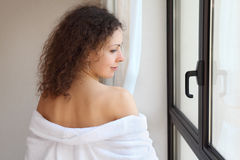 Woman stands near window and removes bathrobe Stock Photography