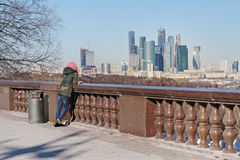 Woman stands on observation deck of the Vorobyovy Gory and watching to the business center `Moscow City` Stock Photography