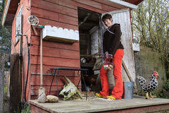 Woman stands outside chicken coop holding eggs in a basket Stock Image