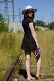 The woman stands on overgrown tracks and she holds the slippers in her hand. A woman in a black dress with straw hat stands on the rails royalty free stock image