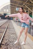 The woman extends her arms to the railroad tracks. stock photos