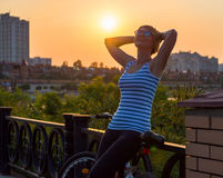 Woman stands and rests after a bike ride, holding her hands behi Stock Image