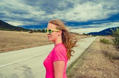 Woman stands on a road and watching mountains royalty free stock image