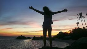 Woman stands on the rock raises her hands during sunset on tropical beach. slow motion. 1920x1080. Hd stock video footage