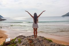 Woman stands on rocks in front of the ocean Royalty Free Stock Images