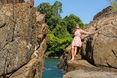 Woman stands among the rocks of the sea coast. Stock Photo