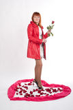 Girl with a rose. Woman stands among rose petals on white Stock Photography