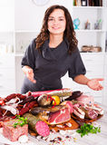 Woman stands with smoked products Stock Photo