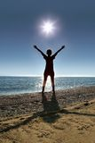 Woman stands on socks ashore opposite sun Royalty Free Stock Image