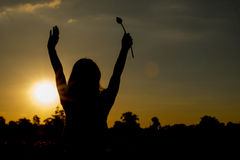 Woman stands at sunset happily. Royalty Free Stock Image