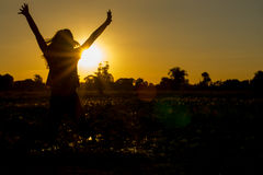 Woman stands at sunset happily. Royalty Free Stock Photos