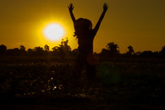 Woman stands at sunset happily. Royalty Free Stock Photo