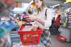 Woman stands at the supermarket`s cash register and discharges the goods out of the basket royalty free stock image