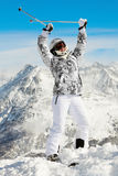 Woman stands throwing up hands with ski poles Stock Photos