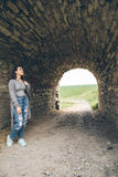 Woman stands in tunnel of old castle Stock Image