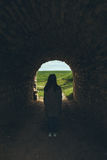 Woman stands in tunnel of old castle Royalty Free Stock Images