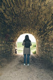 Woman stands in tunnel of old castle Stock Photo