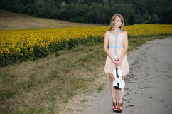 Woman stands with vilolin by country road Royalty Free Stock Photo