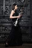 A woman stands with a violin sideways to the photographer Royalty Free Stock Images