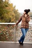 Woman stands waiting at the bridge railing Royalty Free Stock Photo