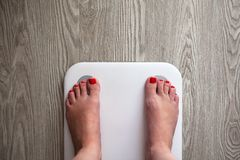 Woman stands on white modern electronic sensor scales. Only feet are visible. Scales stand on gray wooden floor. Space for text. stock image