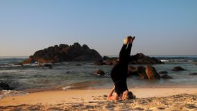 Woman stands in yoga pose supported shoulder stand on beach. Fit woman stands in yoga supported shoulder stand on morning beach against ocean waves and brown stock footage