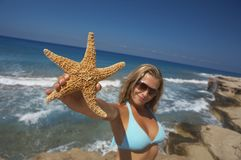 Woman with starfish. Young woman holding up a starfish in front of the beautiful ocean Royalty Free Stock Photos