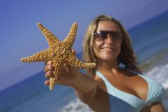 Woman with starfish. Young woman holding up a starfish in front of the beautiful ocean Stock Images