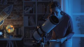 Woman stargazing with a professional telescope stock image