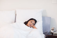 Woman staring at alarm clock Stock Photography