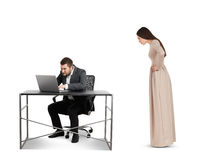 Woman staring at businessman with laptop. Angry women staring at concentrated businessman with laptop. isolated on white background Stock Photography