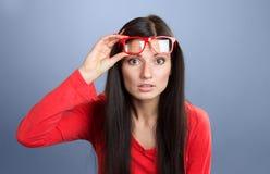 Woman staring at camera. Woman lifting eyeglasses and staring at camera, studio shot on gray background Royalty Free Stock Photography