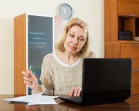 Woman staring documents with laptop Royalty Free Stock Image