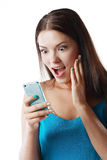 Woman staring at her mobile. Young brunette shocked woman staring at her mobile phone in disbelief royalty free stock image