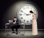 Woman staring at man with laptop. Young beautiful women staring at men with laptop. photo in dark room with big white clock on the wall Royalty Free Stock Photo