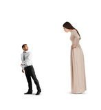 Woman staring at outgoing man. Discontented women in long dress staring at outgoing small man. isolated on white background Royalty Free Stock Images