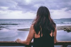 Woman staring at the sea. With her back facing the camera Stock Image