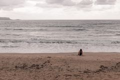 Woman staring at the sea. With her back facing the camera Royalty Free Stock Photos