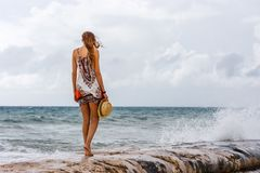 Woman staring at the sea at Playa del Carmen beach, Quintana Roo. Woman with a hat in her hands staring at the sea at Playa del Carmen beach, Quintana Roo Stock Photography