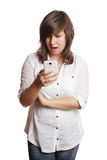 Woman staring at smartphone in shock. Open-mouthed young woman staring at smartphone in disbelief or shock Royalty Free Stock Image