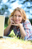 Woman staring into space. While working outside on laptop computer Stock Photography
