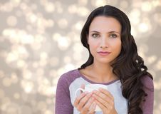 Woman staring straight ahead with white mug against cream bokeh Royalty Free Stock Image