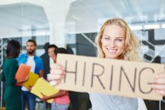 Woman in start-up holding sign. As hiring advertising Stock Images