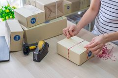 Woman, Start up small business. Owner packing cardboard box at workplace. Prepare parcel packing box of product for deliver stock photo