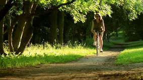 Woman starting to ride a bike through a green grass park over trees and sunset stock video footage