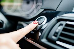 Woman starts the car engine with start-stop button Royalty Free Stock Photos