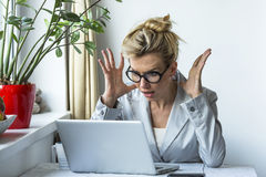 Woman in a state of shock sitting near the computer. Stock Photo