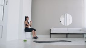 A woman in a static position carries out a grueling exercise leaning against a wall in a sitting position. Endurance. Training stock footage